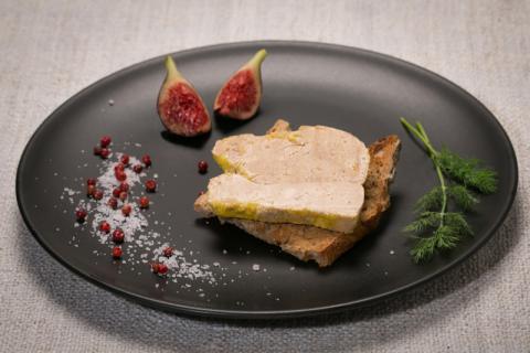 Photo d'une tranche de foie gras sur du pain grillé dans une assiette noire et décorée